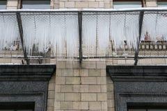 在一个栅格的冰柱在大厦下在冬天 库存照片