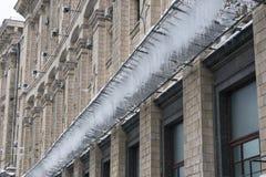 在一个栅格的冰柱在大厦下在冬天 免版税库存图片