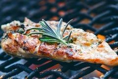 在一个格栅的烤鸡内圆角用香料和草本 在火焰状格栅的用卤汁泡的鸡胸脯与菜 健康的食物 免版税图库摄影