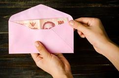 在一个桃红色信封的泰国钞票 免版税库存照片