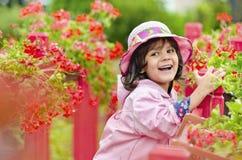 在一个桃红色帽子和雨衣的小女孩关闭 免版税库存图片