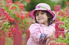在一个桃红色帽子和雨衣的小女孩关闭 免版税库存照片