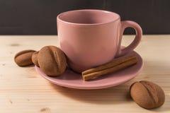 在一个桃红色杯子的咖啡用在土气桌上的曲奇饼 免版税库存图片