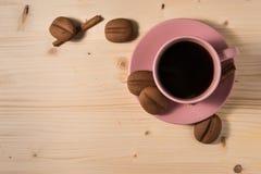 在一个桃红色杯子的咖啡用在土气桌上的曲奇饼 图库摄影