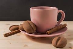 在一个桃红色杯子的咖啡用在土气桌上的曲奇饼 免版税库存照片
