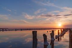 在一个桃红色盐湖,桃红色盐的提取的一个前矿的日落 木钉行长满与盐 库存照片
