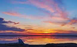 在一个桃红色盐湖,桃红色盐的提取的一个前矿的日落 木钉行长满与盐 图库摄影
