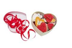 在一个桃红色箱子的心脏曲奇饼有在充满裁减路线、情人节和爱的白色背景隔绝的红色丝带的 库存图片