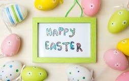 在一个框架的愉快的复活节卡片用五颜六色的鸡蛋 库存照片