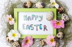在一个框架的愉快的复活节笔记用鹌鹑蛋 免版税库存照片