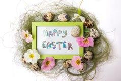 在一个框架的愉快的复活节笔记用鹌鹑蛋 免版税库存图片