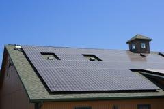 在一个棕色房子的太阳电池板 免版税库存图片
