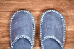 在一个棕色木地板上的蓝色家庭拖鞋 免版税库存图片