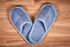在一个棕色木地板上的蓝色家庭拖鞋 库存照片