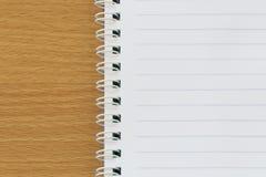 在一个棕色木地板安置的空的笔记本的黑线 图库摄影