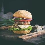 在一个棕色木板的乳酪汉堡 免版税库存图片