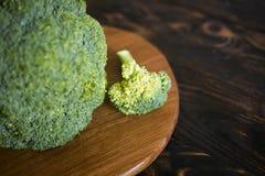 在一个棕色木背景和切板的硬花甘蓝圆白菜 免版税库存照片