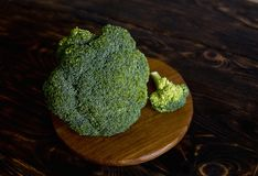 在一个棕色木背景和切板的硬花甘蓝圆白菜 库存照片