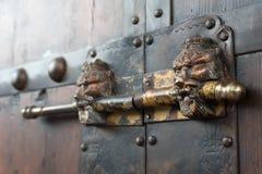 在一个棕色木门的狮子顶头中国门衣物柜 免版税库存图片