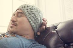 在一个棕色沙发的亚洲人睡眠 免版税库存图片