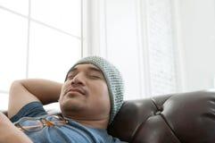 在一个棕色皮革沙发的亚洲人睡眠 库存照片