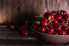 在一个棕色碗的樱桃在一张木桌上 您的文本的空位 免版税图库摄影