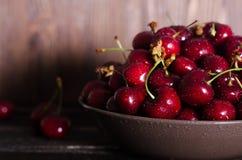 在一个棕色碗的樱桃在一张木桌上 您的文本的空位 免版税库存照片