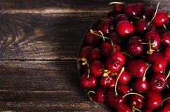 在一个棕色碗的樱桃在一张木桌上 您的文本的空位 图库摄影