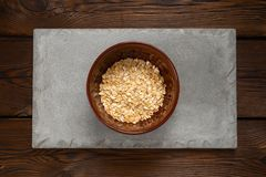 在一个棕色碗的燕麦片在木背景的一块混凝土瓦 免版税库存图片