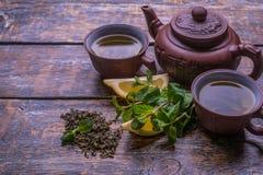 在一个棕色罐的绿茶,杯子用茶,薄菏,柠檬,在黑暗的老背景的姜 免版税库存图片