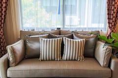 在一个棕色织品沙发的枕头 免版税库存照片