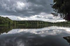 在一个森林中间的湖有反映的暴风云 库存图片