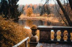 在一个森林和一个湖的秋天风景有一个老阳台的 库存照片
