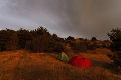 在一个森林和一条双重彩虹附近的两个帐篷在天空 免版税图库摄影