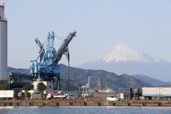 在一个榨油工厂的起重机与富士山 库存图片