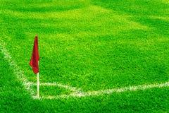 在一个橄榄球场的红色壁角旗子与明亮的新鲜的绿色草皮草和白色足球接触线 图库摄影