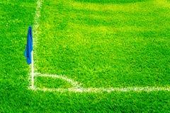 在一个橄榄球场的蓝色壁角旗子与明亮的新鲜的绿色草皮草和白色足球接触线 免版税图库摄影