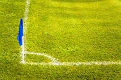 在一个橄榄球场的蓝色壁角旗子与绿色草皮草 免版税库存图片