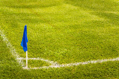 在一个橄榄球场的蓝色壁角旗子与绿色草皮草 免版税库存照片
