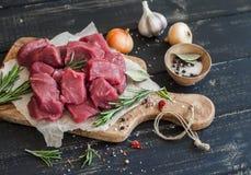 在一个橄榄色的委员会、香料、草本和菜的新鲜的未加工的切好的牛肉在黑暗的木背景 库存照片