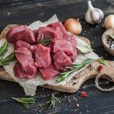 在一个橄榄色的委员会、香料、草本和菜的新鲜的未加工的切好的牛肉在黑暗的木背景 免版税库存图片