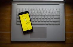 在一个残破的手机的Snapchat app坐膝上型计算机 库存图片