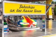 在一个民间节日的碰撞用汽车与意味到乘驾的购买票在薪水窗口的德国文本 图库摄影