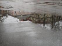 在一个水坑的反射在老城市灰色沥青安置绿色和桃红色,城市水池 库存照片