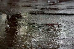 在一个水坑的雨珠在沥青 库存照片
