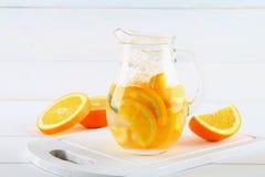 在一个水罐的橙色戒毒所水在一张白色木桌上 健康食物,饮料 库存图片