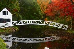 在一个池塘和一个房子的桥梁银行的在水中反射了在秋天公园 图库摄影