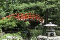 在一个池塘的一座红色桥梁在森林里 免版税库存照片