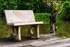 在一个池塘附近的一条孤零零石长凳在庭院里 库存图片