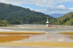 在一个污染的湖中间的被充斥的和被放弃的教会 图库摄影